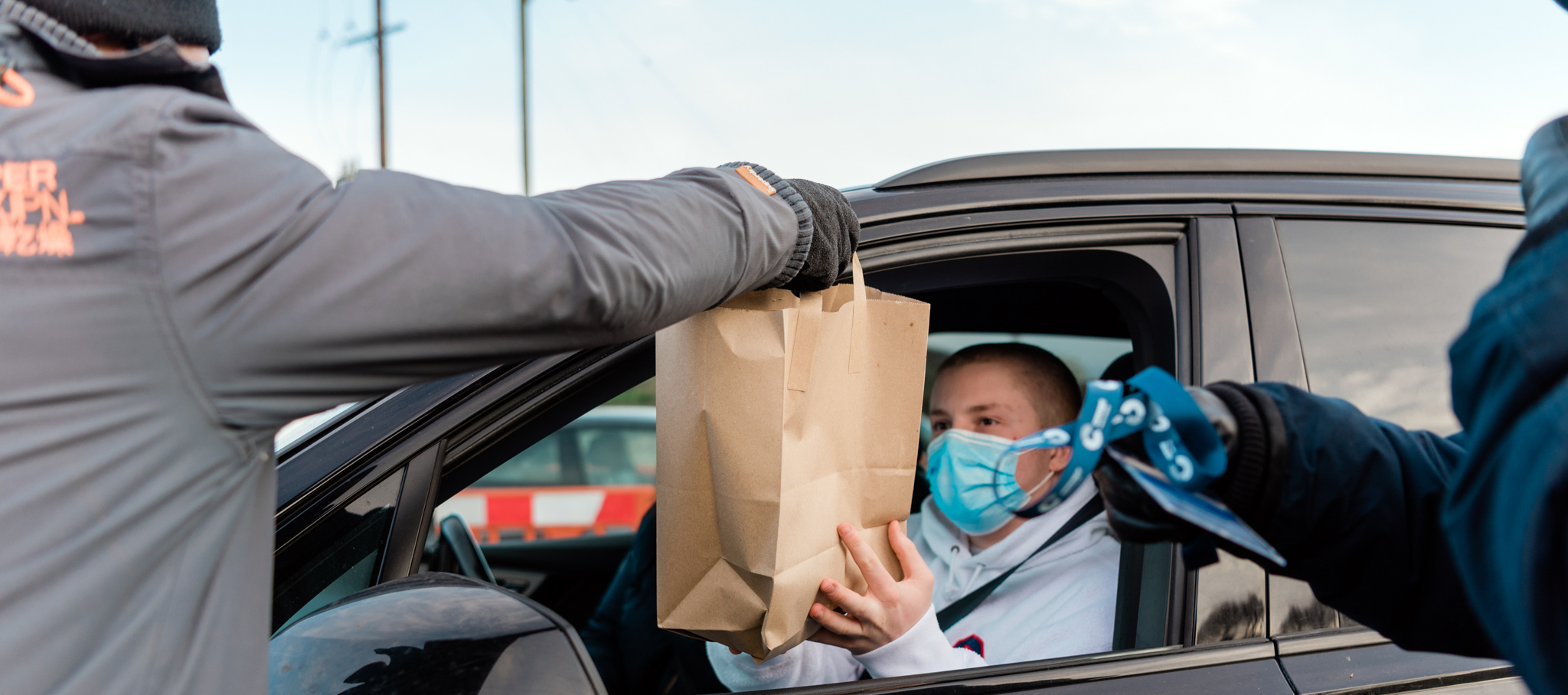 Young person in mask in a car being given takeaway to deliver to client