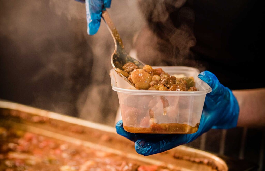 volunteer with gloved hands putting food into takeaway container